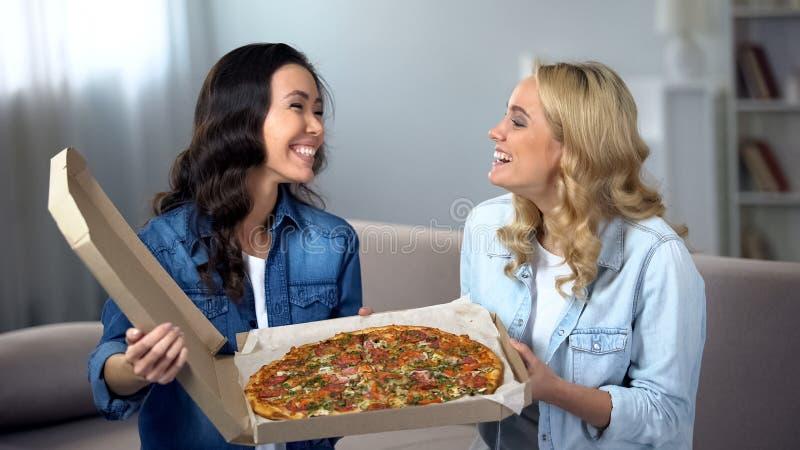 Gladlynta kvinnor med enorm pizza som hemma skrattar och har gyckel, snabbmat royaltyfri fotografi
