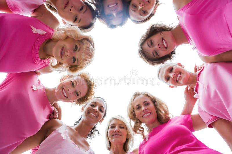 Gladlynta kvinnor som ler i bärande rosa färger för cirkel för bröstcancer royaltyfria bilder