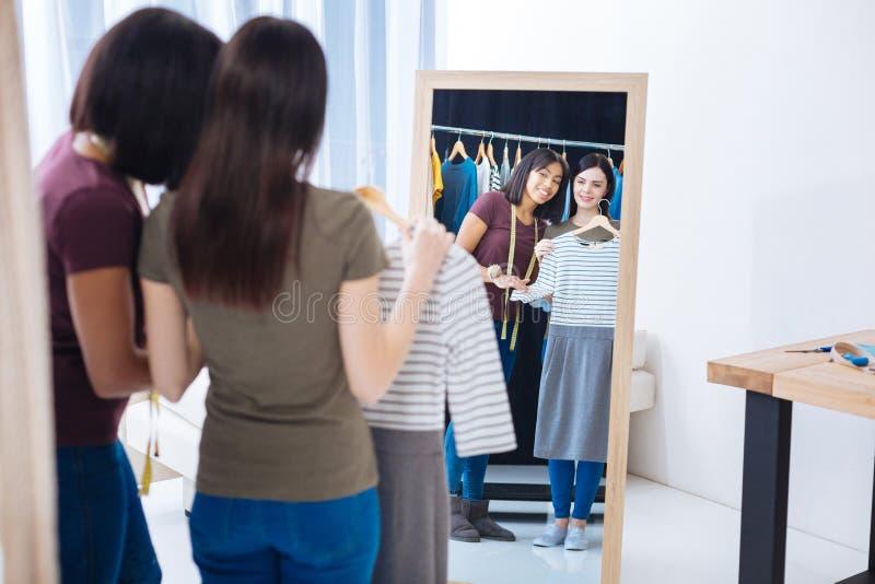 Gladlynta kvinnor som ser deras reflexion i spegeln och le fotografering för bildbyråer