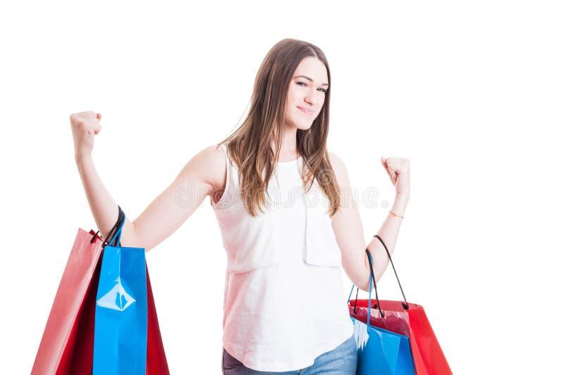 Gladlynta le hållande shoppingpåsar för kvinna agerar som en vinnare royaltyfri bild