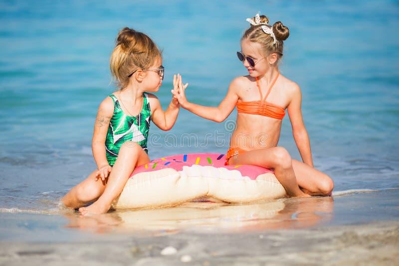 Gladlynta lyckliga flickor har en vila på havet royaltyfri foto