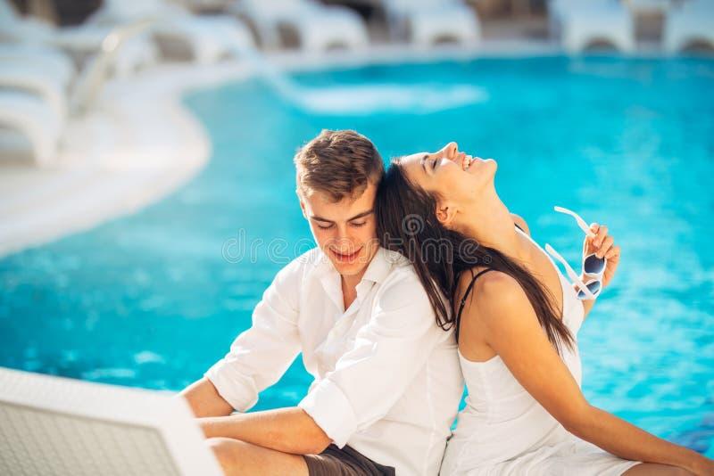 Gladlynta lyckliga par som tycker om brunnsorten, semestrar i lyxig sommarsemesterort Bröllopsresatur Årsdagberöm royaltyfri fotografi