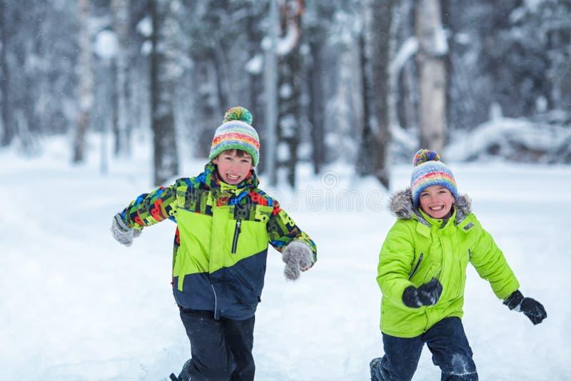 Gladlynta lyckliga pojkar som spelar i vinter, parkerar, arkivfoton