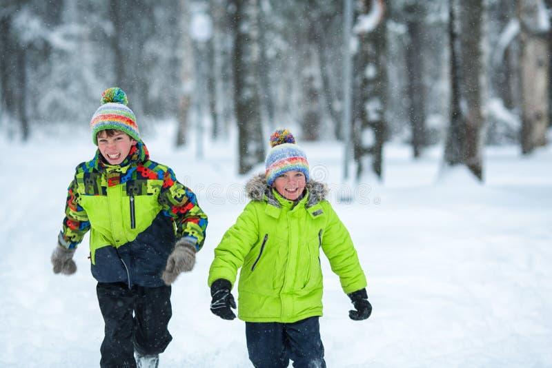 Gladlynta lyckliga pojkar som spelar i vinter, parkerar, royaltyfria bilder