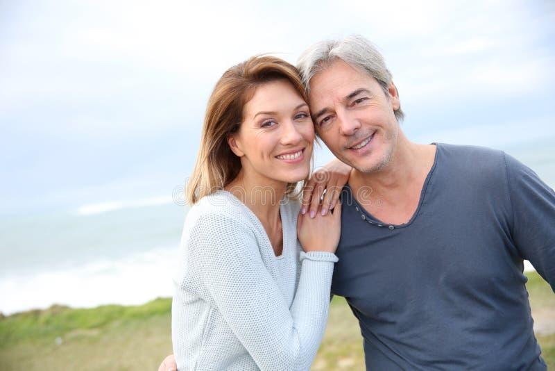 Gladlynta medelåldersa par vid sjösidan arkivfoto