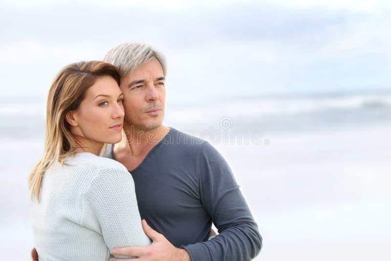 Gladlynta medelåldersa par vid stranden arkivbilder