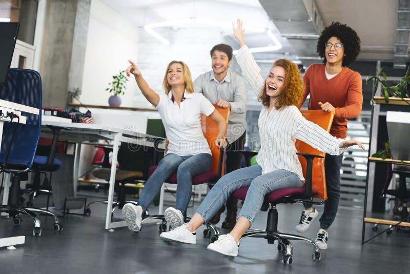 Gladlynta millennials som rider på kontorsmöblemang och att ha gyckel på arbete royaltyfria bilder