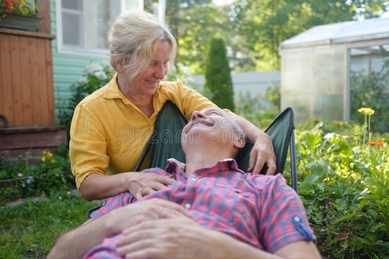 Gladlynta mogna par som vilar i grön sommarträdgård royaltyfria foton