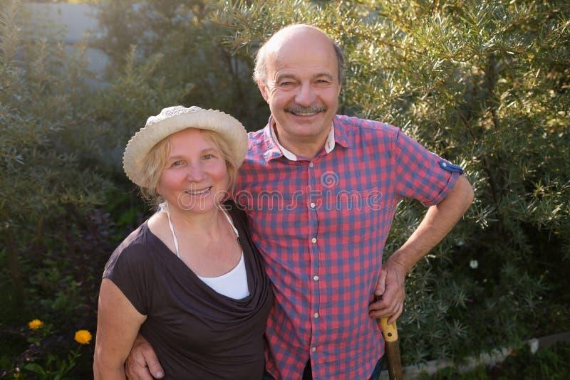 Gladlynta mogna par som vilar i grön sommarträdgård arkivfoton