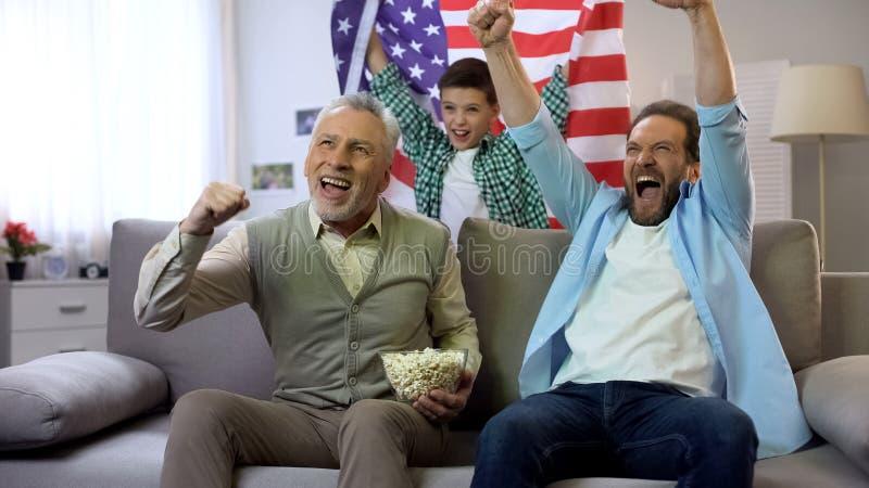 Gladlynta multiagefotbollfans som ?r lyckliga med det amerikanska laget som g?r po?ng m?let, fritid royaltyfri bild