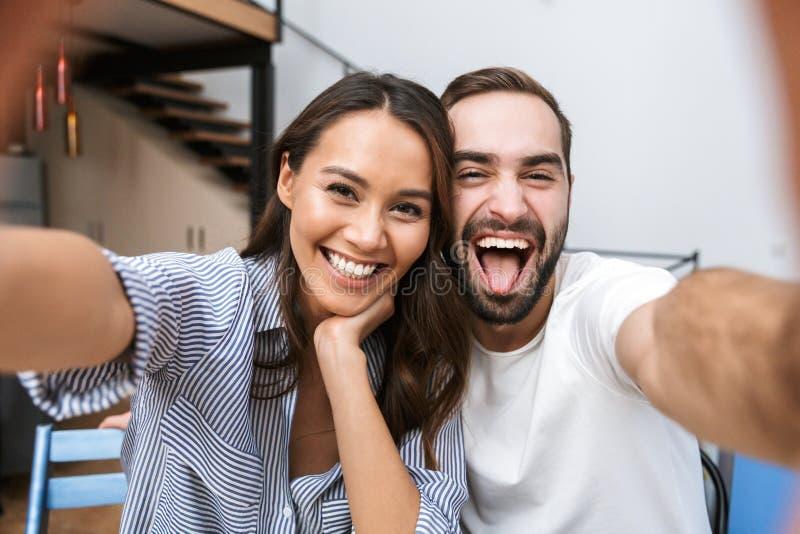 Gladlynta multietniska par som tar en selfie royaltyfria bilder