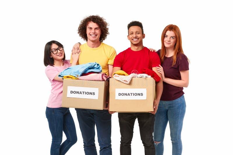 Gladlynta multietniska volontärer med donationer arkivbild