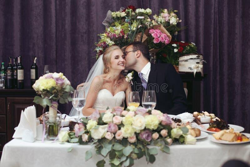 Gladlynta nygift personpar, make och fru som kysser och rostar arkivfoto