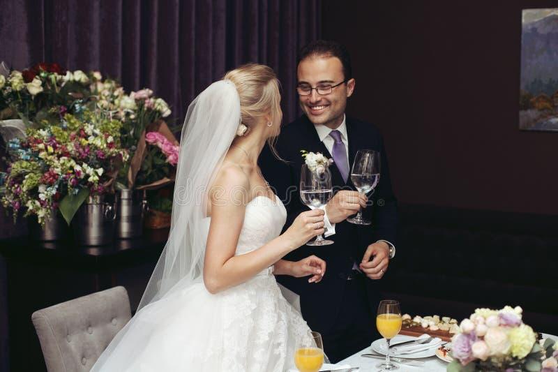 Gladlynta nygift personpar som dricker champagne och rostar på wedd arkivbild