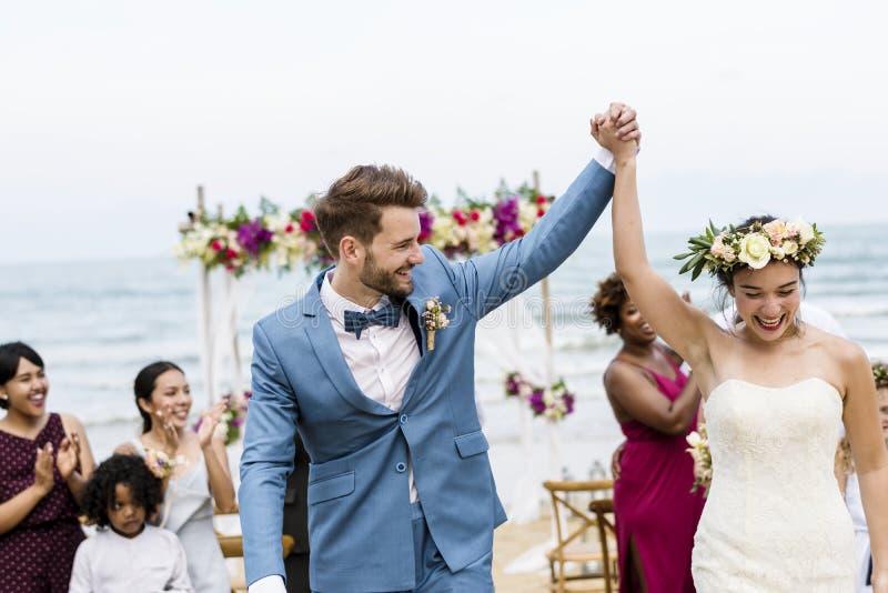 Gladlynta nygifta personer på strandbröllopceremoni royaltyfri fotografi