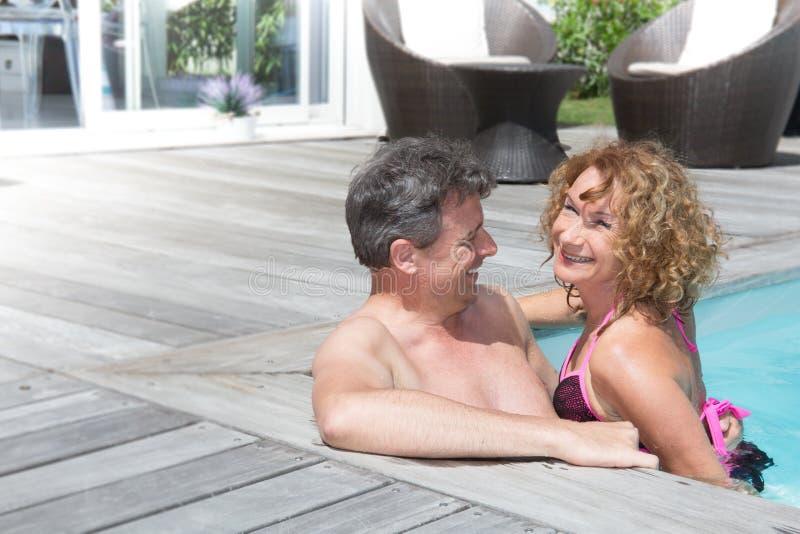 Gladlynta och charmiga par som har gyckel i simbassäng royaltyfri foto