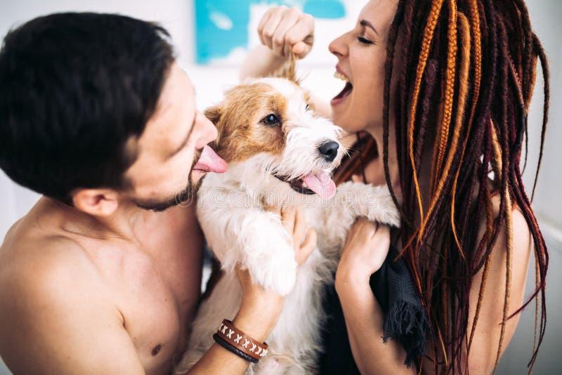 Gladlynta och lyckliga par och hunden som ler och visar tongu royaltyfri foto