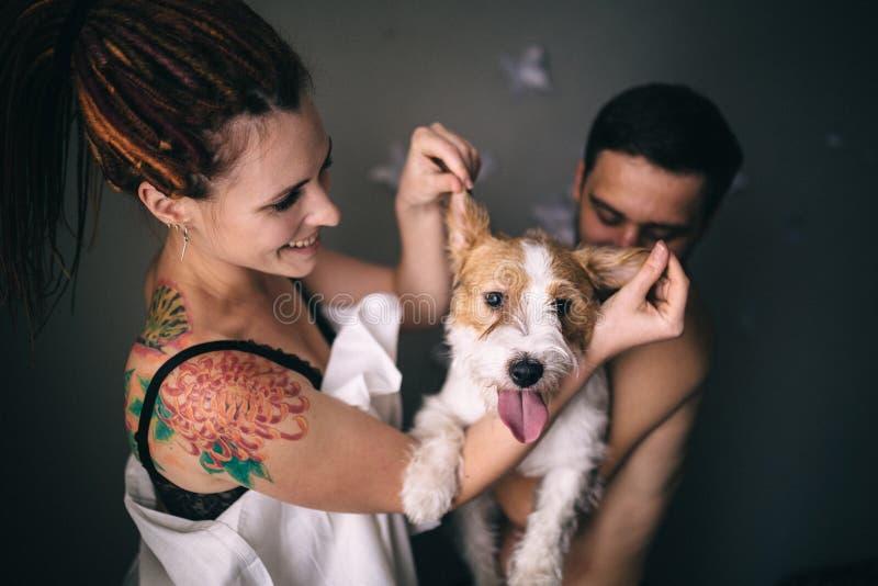 Gladlynta och lyckliga par och hunden som ler och visar tongu arkivfoton