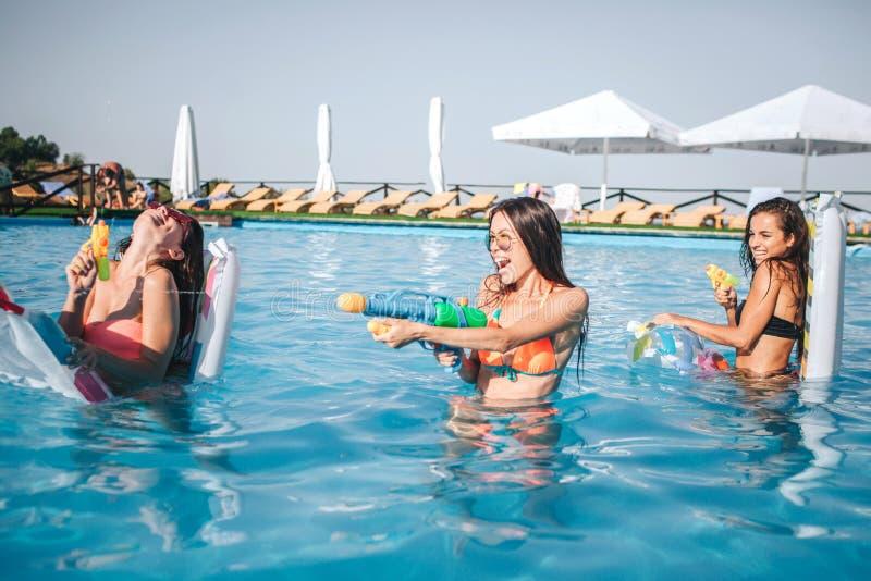Gladlynta och roliga modeller som spelar i simbassäng De rymmer vattenvapen, i händer och att använda det Kvinna två är mot arkivbild