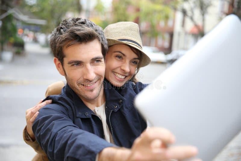 Gladlynta par av turister som tar selfie med minnestavlan arkivbild