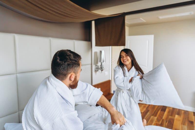 Gladlynta par har gyckel i sovrummet som hemma sl?ss med stora kuddar arkivfoto