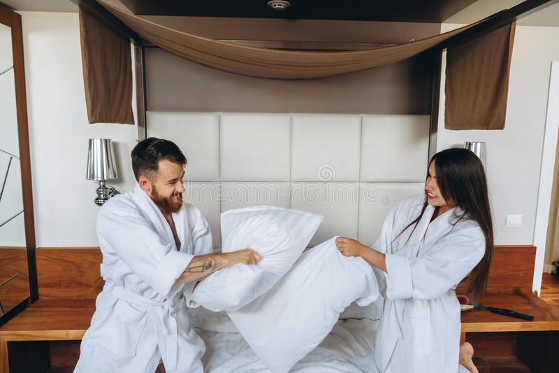 Gladlynta par har gyckel i sovrummet som hemma sl?ss med stora kuddar royaltyfri fotografi