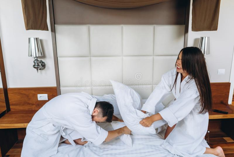 Gladlynta par har gyckel i sovrummet som hemma sl?ss med stora kuddar arkivbilder