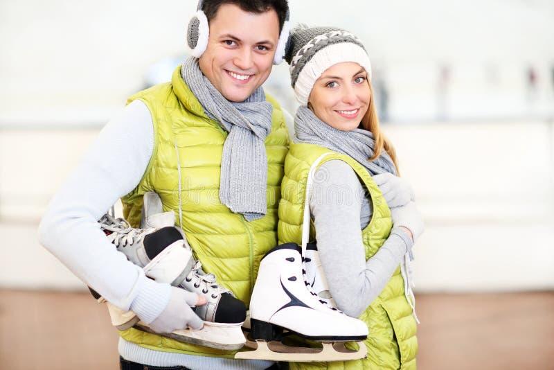 Gladlynta par i den åka skridskor isbanan arkivbild