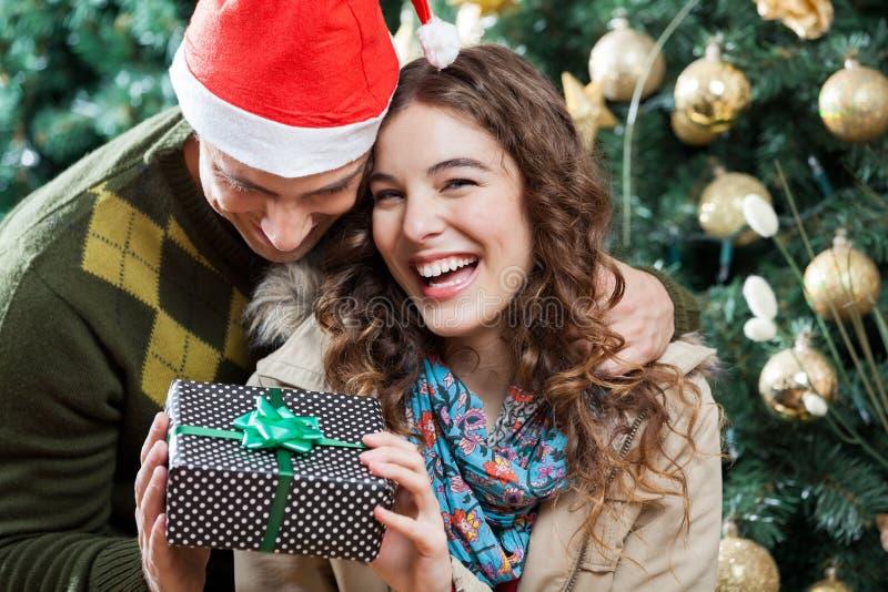 Gladlynta par med julklapp i lager royaltyfria bilder
