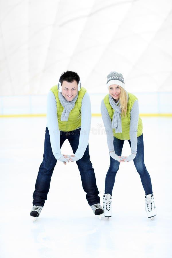 Gladlynta par på den åka skridskor isbanan arkivbild