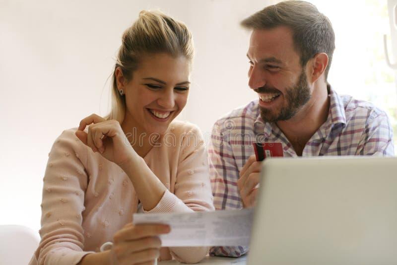 Gladlynta par som betalar räkningar royaltyfria bilder