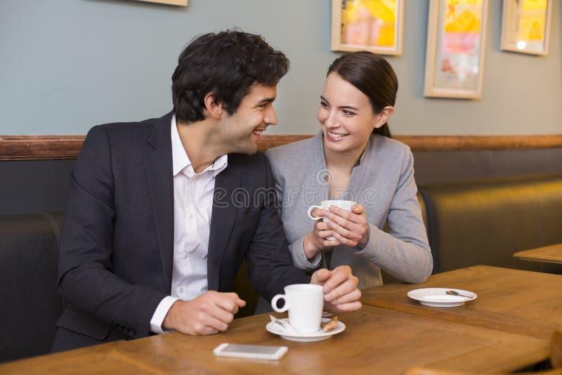 Gladlynta par som flörtar på cafeteriatabellen arkivbild