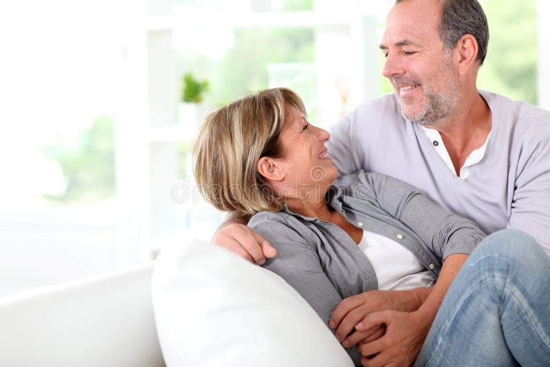 Gladlynta par som hemma omfamnar på soffan royaltyfria bilder