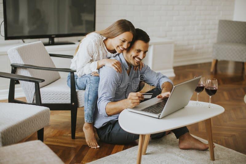 Gladlynta par som hemma söker internet på bärbara datorn fotografering för bildbyråer