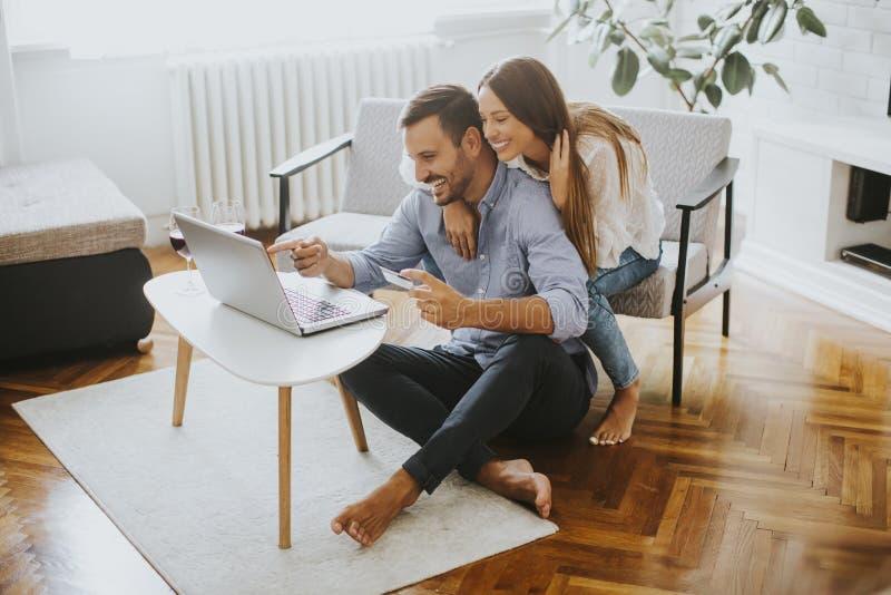 Gladlynta par som hemma söker internet på bärbara datorn arkivfoto