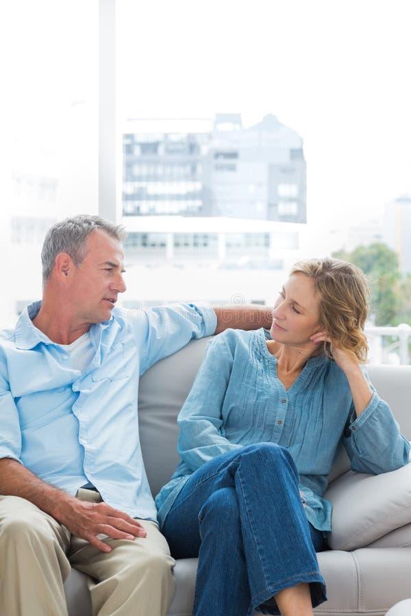 Gladlynta par som kopplar av på deras soffa som har en pratstund royaltyfria foton