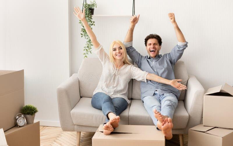 Gladlynta par som kopplar av på det Sofa Celebrating Moving To New huset royaltyfri fotografi