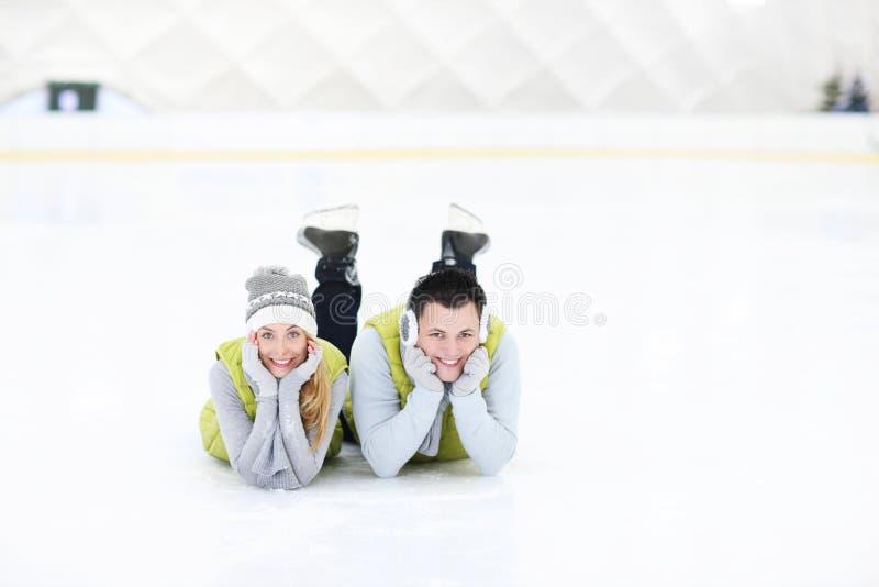 Gladlynta par som ligger på den åka skridskor isbanan arkivbild
