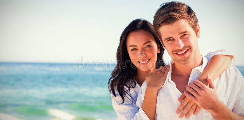 Gladlynta par som omfamnar på stranden arkivbilder