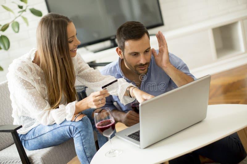Gladlynta par som söker internet och direktanslutet shoppar arkivbild