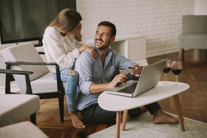 Gladlynta par som söker internet och direktanslutet shoppar arkivfoto