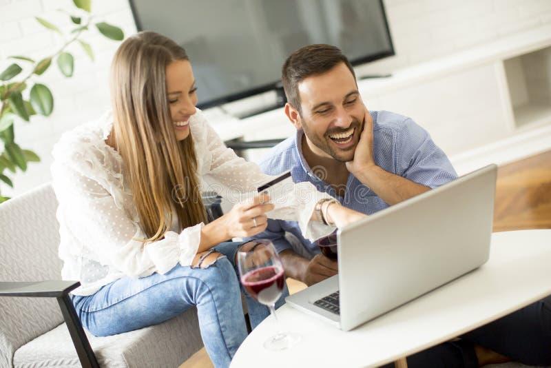 Gladlynta par som söker internet och direktanslutet shoppar fotografering för bildbyråer