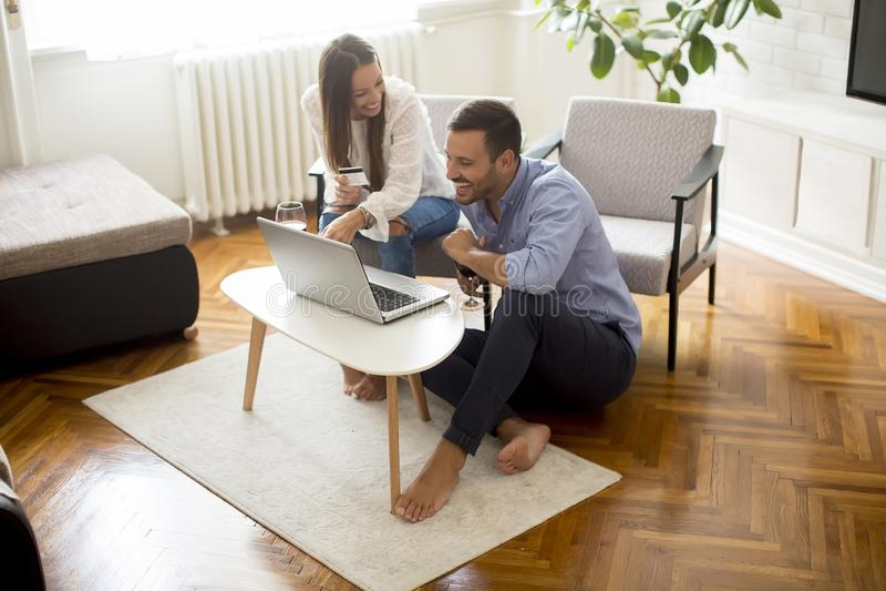 Gladlynta par som s?ker internet och direktanslutet shoppar arkivfoto