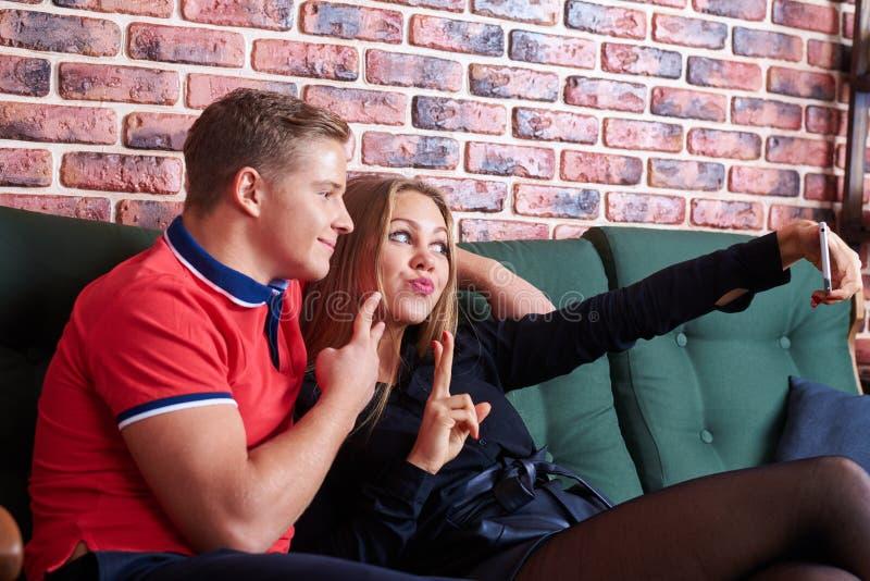 Gladlynta par som tar en selfie med en hemmastadd sittin för smartphone arkivfoto