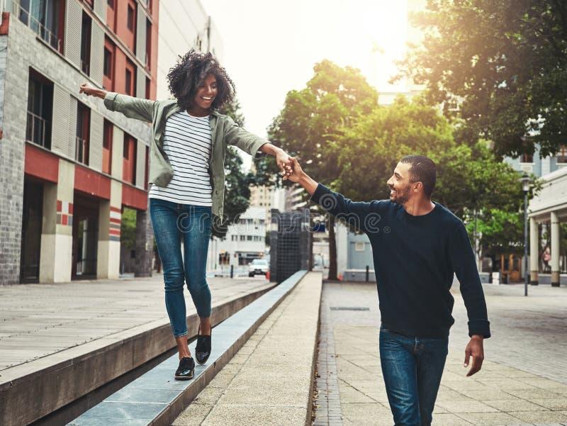 Gladlynta par som tycker om att gå i staden royaltyfria foton
