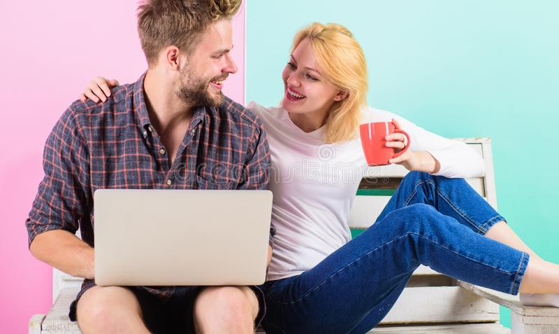 Gladlynta par spenderar fritid med bärbara datorn som surfar rengöringsdukklockavideoen Modernt surfa för internet för ungdomarfr royaltyfria foton