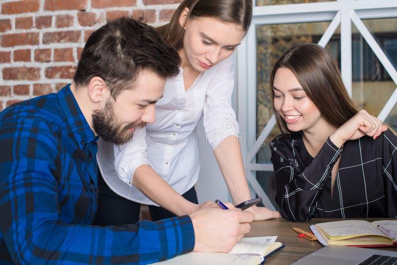 Gladlynta partners som läser på positiv återkoppling för mobiltelefon om deras projekt royaltyfri foto