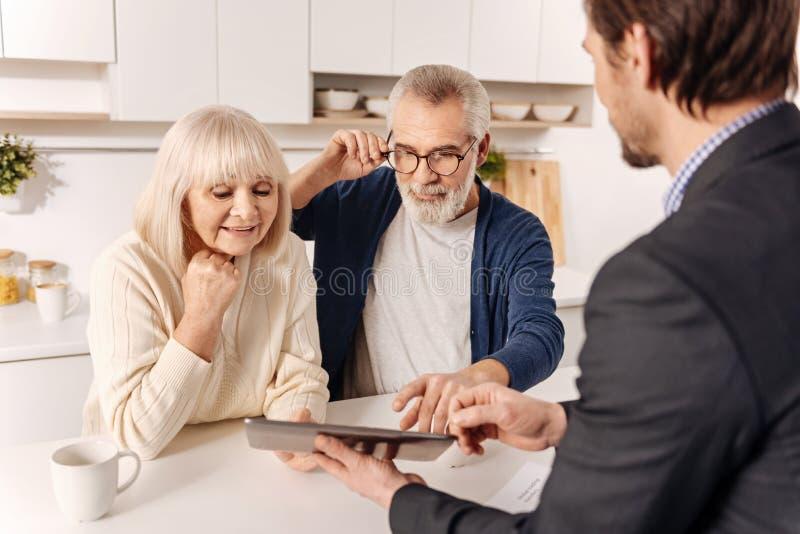 Gladlynta pensionerade par genom att använda grejen med fastighetsmäklaren royaltyfri foto