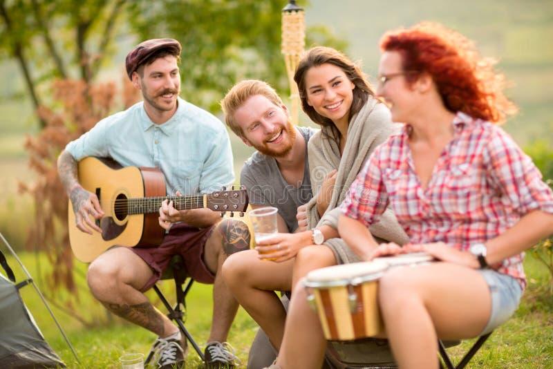 Gladlynta pojkar och flickor som spelar musikinstrument i läger arkivfoto
