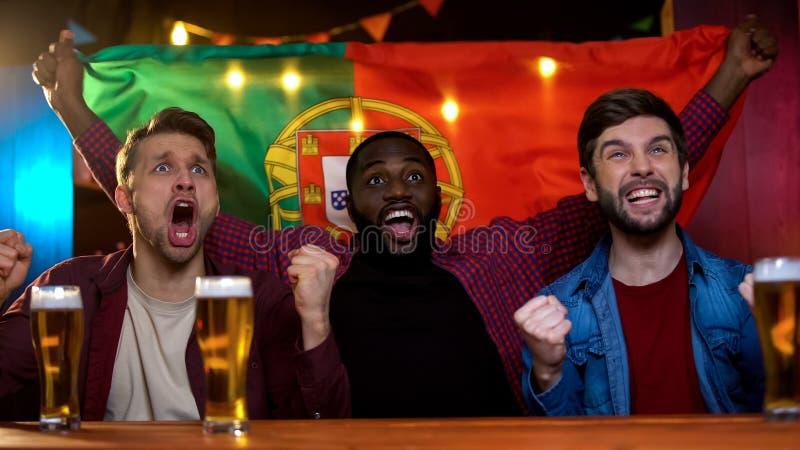 Gladlynta portugisiska blandras- män som firar segern för fotbolllag, vinkande flagga royaltyfria foton